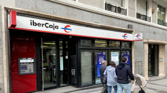 Una familia pasea junto a una oficina de IberCaja en Madrid.