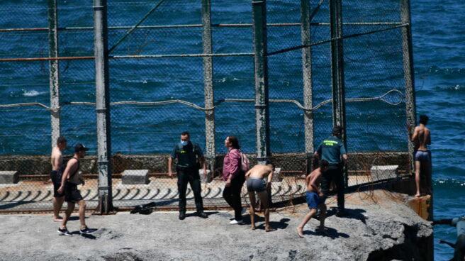 Guardias civiles junto a migrantes marroquíes que han llegado a nado este lunes a Ceuta.