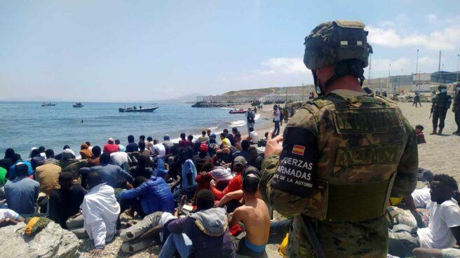 Un soldado del Ejército español vigila a numerosos inmigrantes en Ceuta