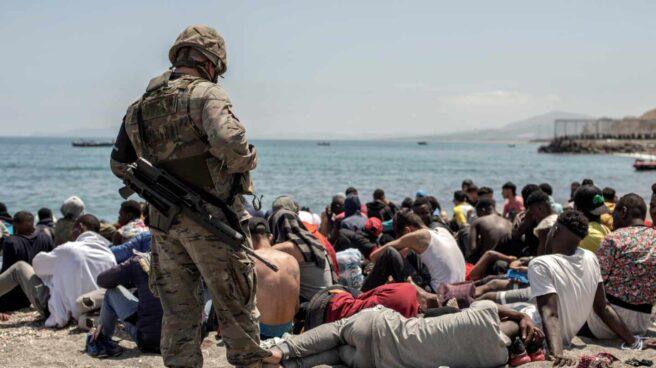 Un militar vigila a los inmigrantes en la playa de Ceuta.