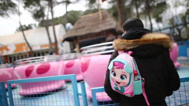 Un hombre con una mochila en un parque de atracciones en Madrid.