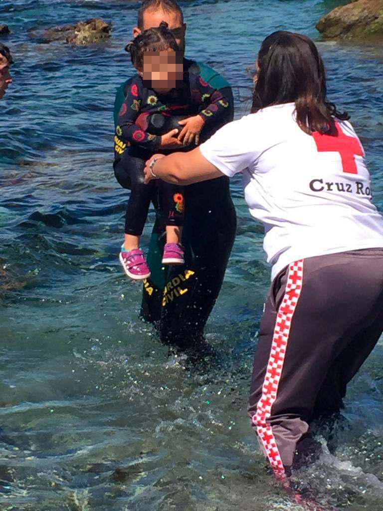 Un Guardia Civil y una miembro de Cruz de Roja ayudan a una niña en Ceuta tras sacarla del agua