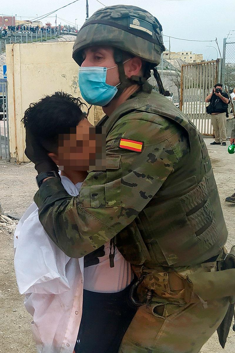 Un militar ayuda a un joven inmigrante tras su llegada a España
