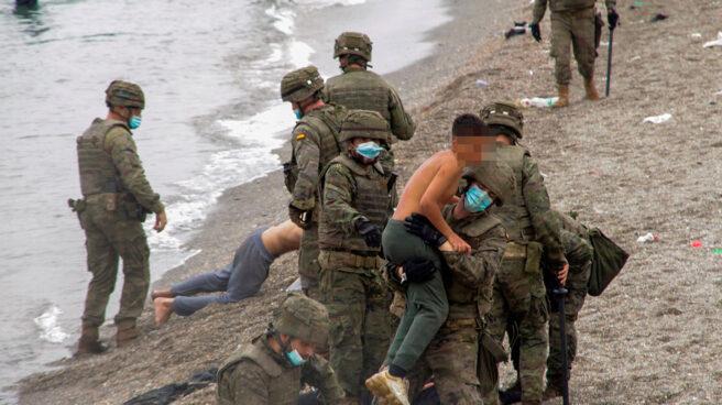 Un miembro del Ejército sostiene en brazos a un joven sin camiseta en la playa del Tarajal