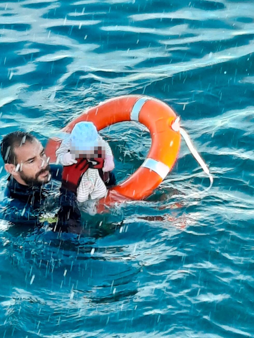 Un Guardia Civil lleva en volandas a un bebé recién nacido en la playa de Ceuta