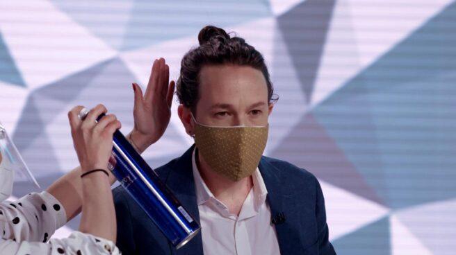 Una peluquera echa laca en el moño de Iglesias antes de participar en el debate de Telemadrid