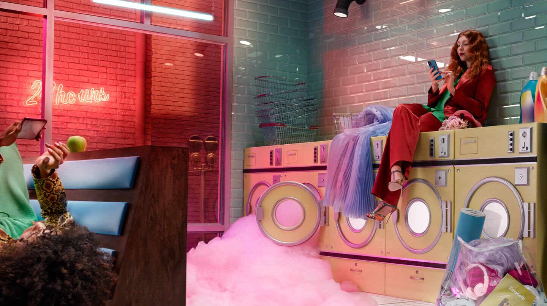Una chica mira su móvil mientras espera en una lavandería.