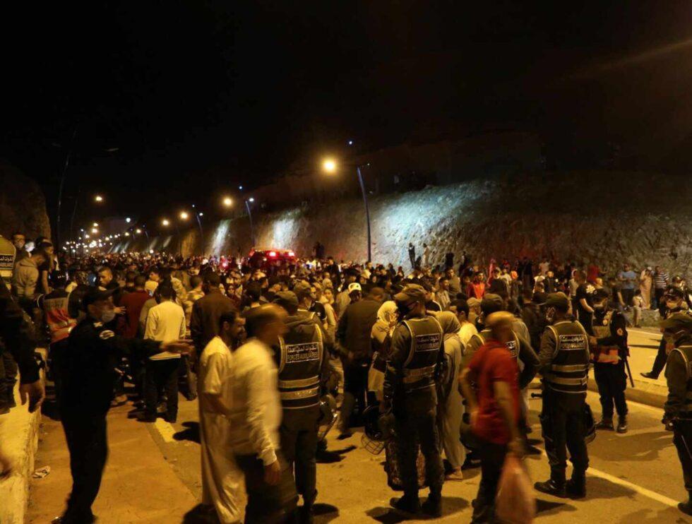 Jóvenes marroquíes esperan el momento de cruzar la frontera, por tierra o agua, este lunes en la localidad de Castillejos