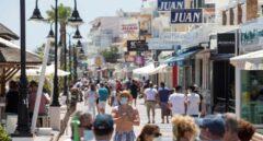 Varias personas disfrutan del buen tiempo paseando por el paseo marítimo de la playa de La Carihuela de Torremolinos