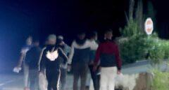 Grupos de jóvenes se desplazan a pie por la carretera que une Tánger con Ceuta para cruzar la frontera con España.