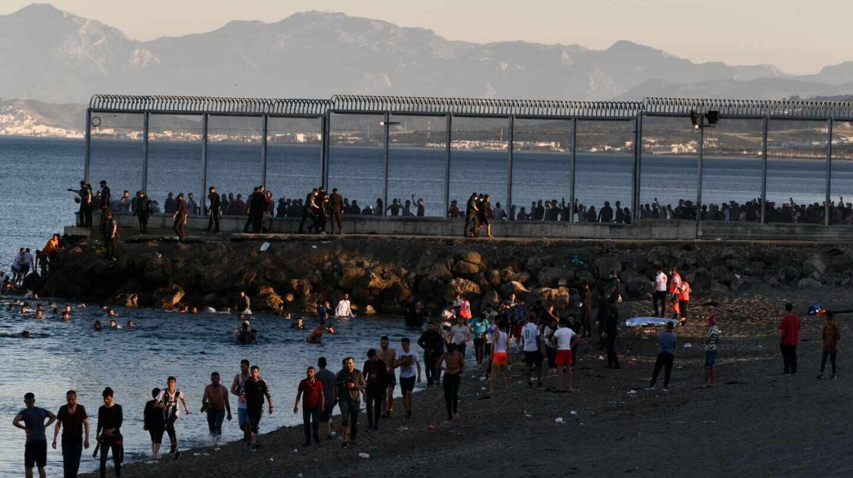 Migrantes marroquíes caminan por la playa del Tarajal, en Ceuta, el pasado lunes por la tarde.