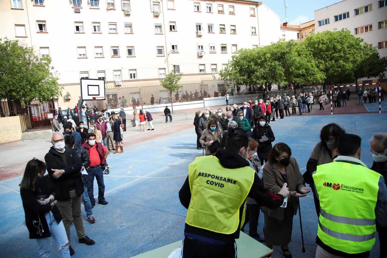Cientos de personas hacen cola para votar en un colegio electoral de Madrid.