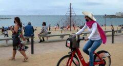 Una mujer pasea en bicicleta por la Barceloneta.