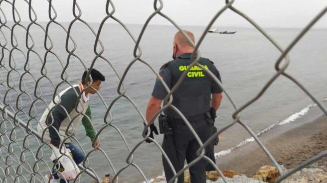 Un Guardia Civil ayuda a uno de los inmigrantes en uno de los espigones fronterizos de Ceuta
