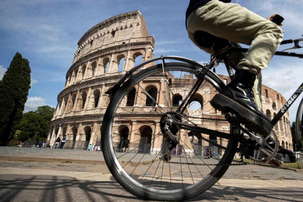 Una persona montada en bicicleta pasea junto al Coliseo de Roma, Italia.