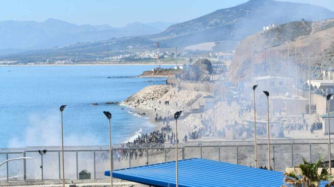 Agentes lanzan gas hacia los inmigrantes que tratan de cruzar la frontera hacia Ceuta desde Marruecos.