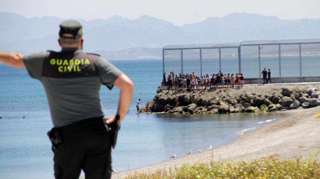 Un guardia civil contempla la llegada de marroquíes a Ceuta este lunes.