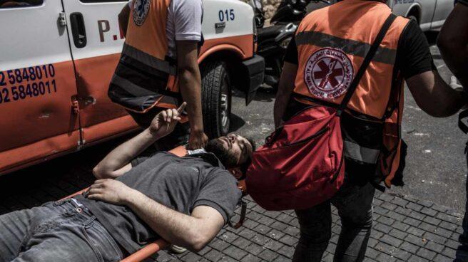 Paramédicos palestinos transportan a un herido durante los enfrentamientos
