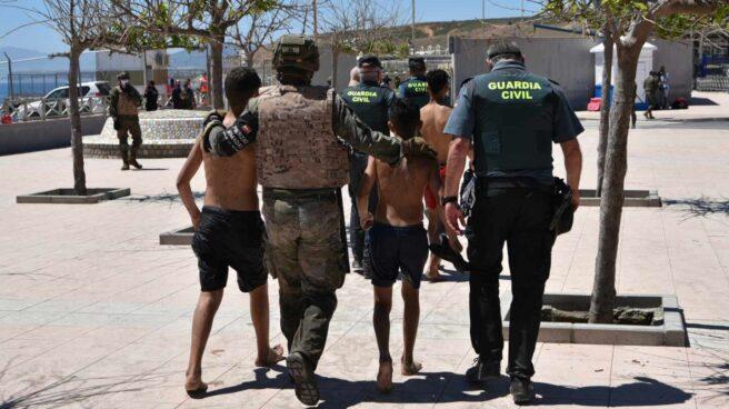 Un militar y un agente de la Guardia Civil ayudan a dos menores migrantes llegados a Ceuta desde Marruecos.