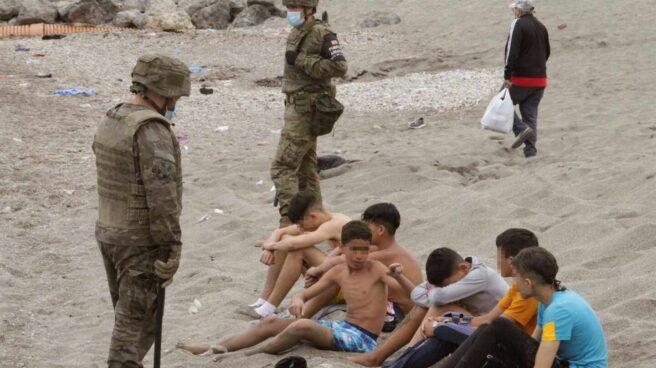 Un soldado, junto a un grupo de menores que cruzaron ilegalmente la frontera con Ceuta.