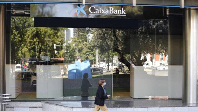 Una mujer pasa por al lado de las oficinas de Caixabank en el Paseo Castellana, en Madrid (España)
