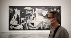 Un trabajador protegido con una mascarilla junto al cuadro de Pablo Picasso 'Guernica' en el Museo Nacional Centro de Arte Reina Sofía.