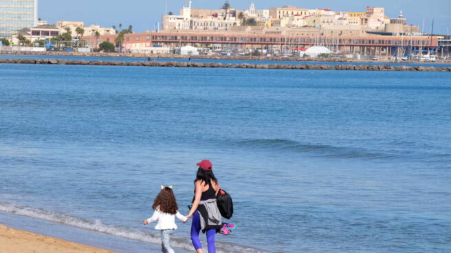 Una mujer y una niña pasean por la playa en Melilla.