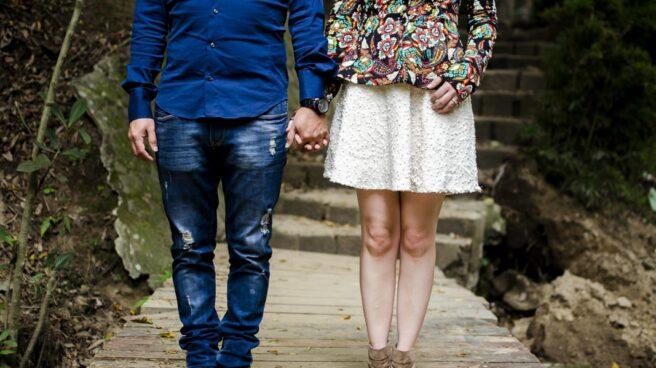 Una pareja de la mano a la que se ve de torso para abajo.