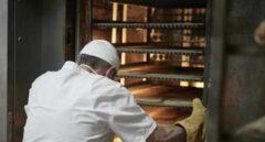 Un trabajador protegido con mascarilla y guantes maneja bandejas para cocer el pan en un obrador.
