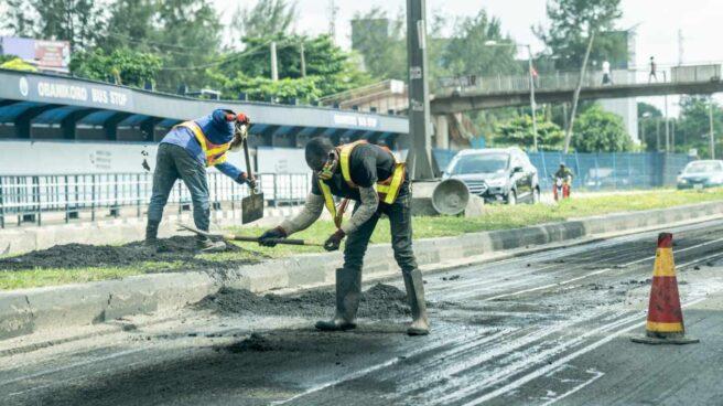 Dos hombres trabajan en la construcción de una carretera en Lagos.