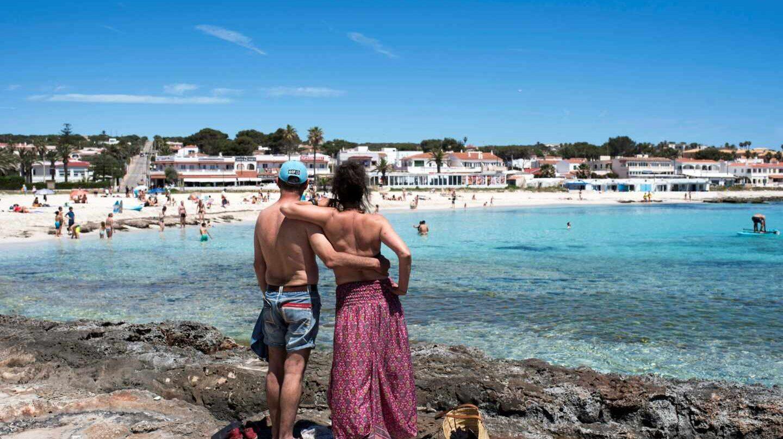 Una pareja observa la playa de Punta Prima en Menorca