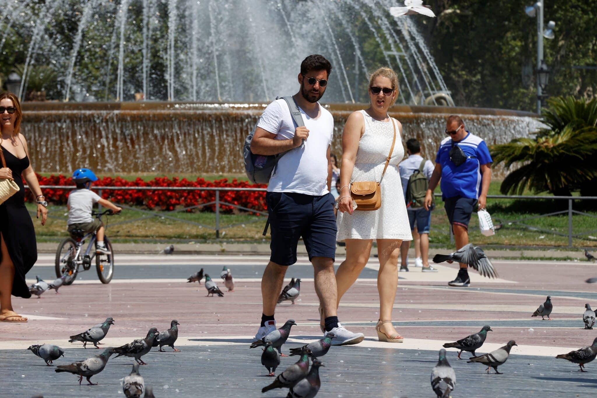 Una pareja pasea sin mascarilla por la plaza de Cataluña este sábado en Barcelona.