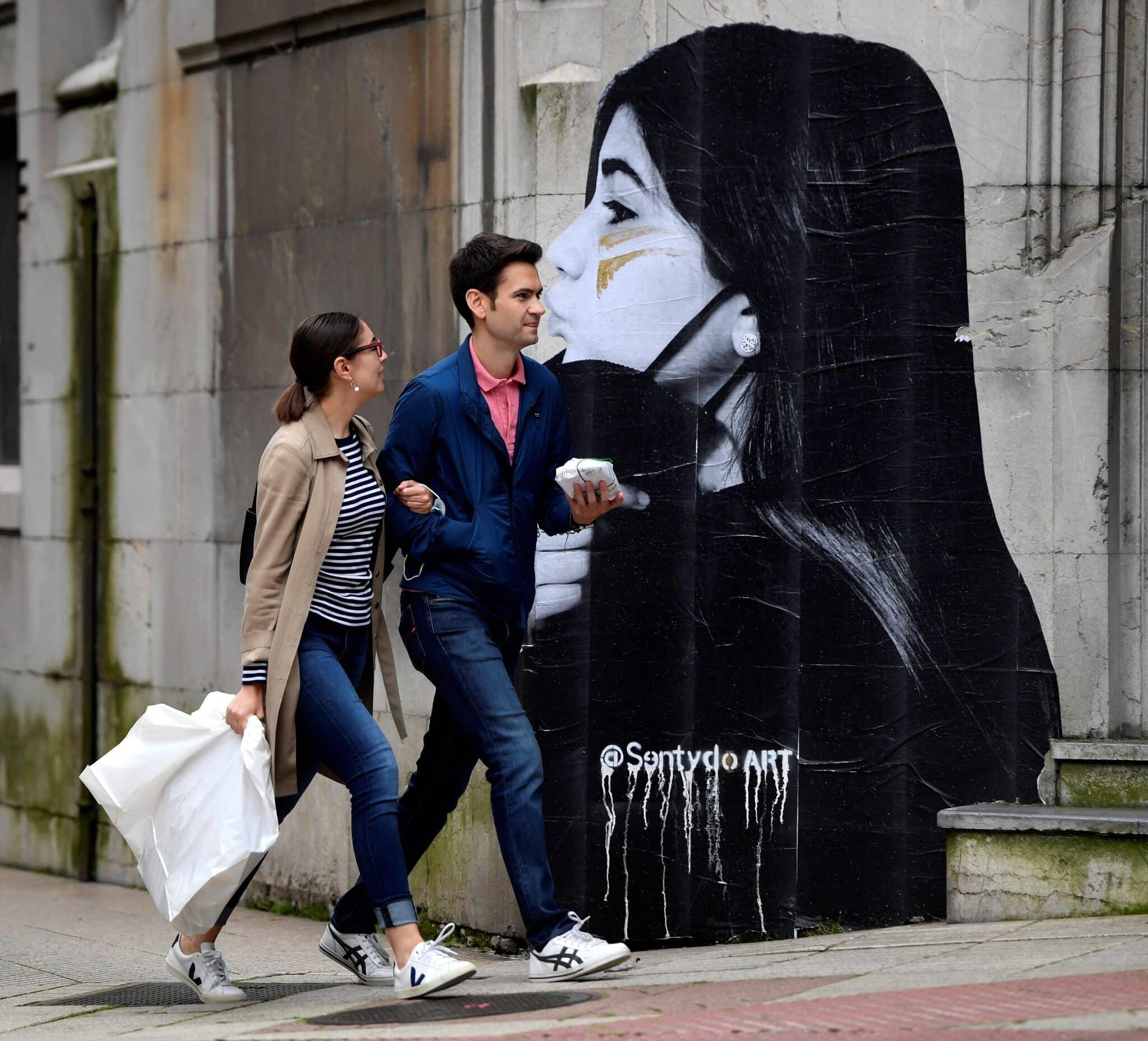 Dos personas caminan con la mascarilla en la mano ante la puerta de entrada de ambulancias del Hospital de la Cruz Roja, este sábado en Oviedo.