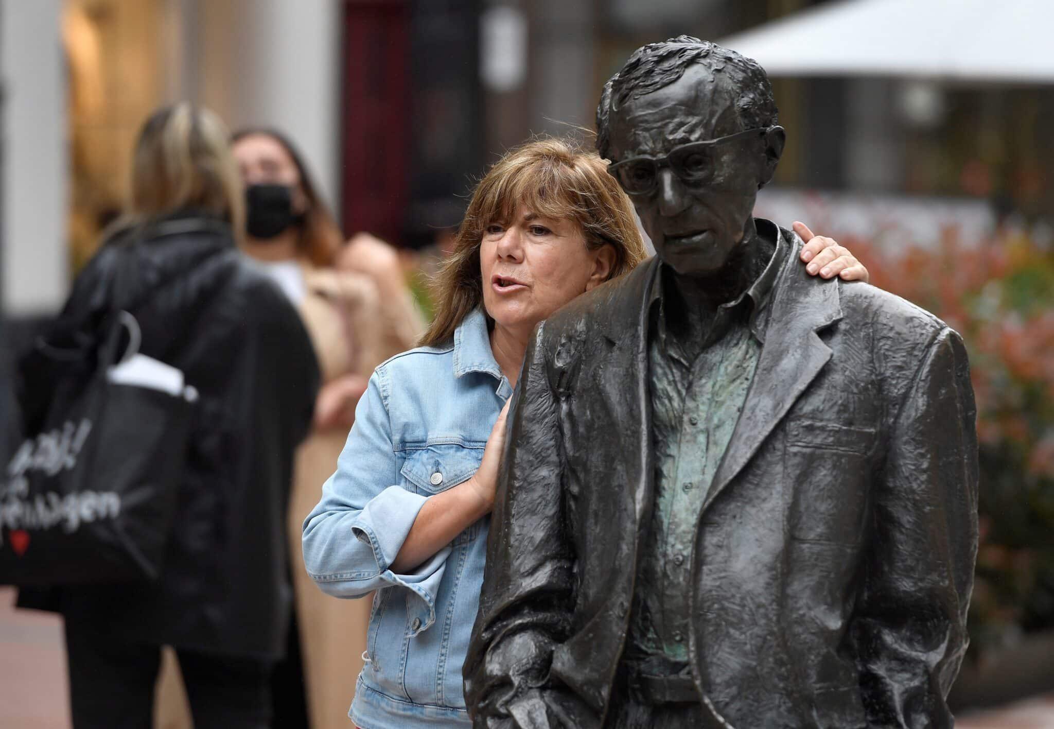 Una mujer sin mascarilla se toma un fotrografía junto a la estatua del cineasta estadounidense Woody Allen.