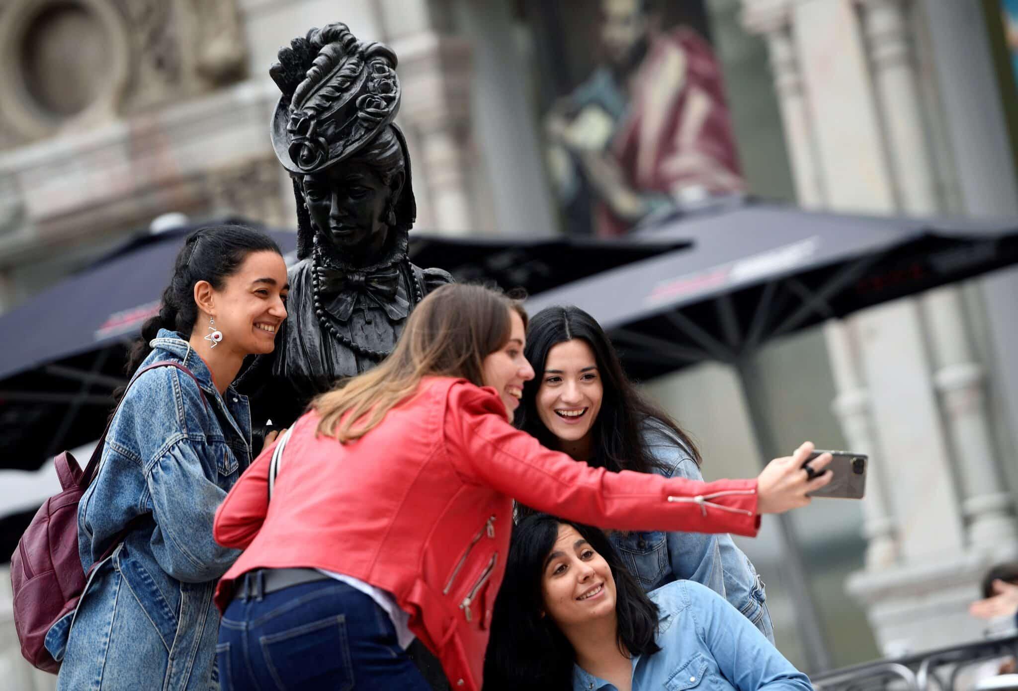 """Turistas sin mascarilla se toman una fotografía junto a la estatua de la Regenta de """"Clarín"""", este sábado en Oviedo."""