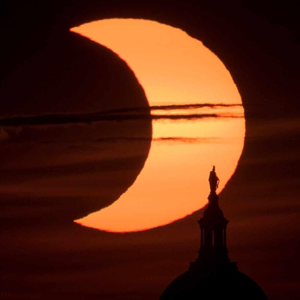 El eclipse, con la estatua de la Libertad del Capitolio de Washington en primer plano