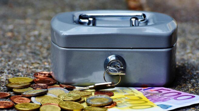Monedas y billetes junto a un cofre