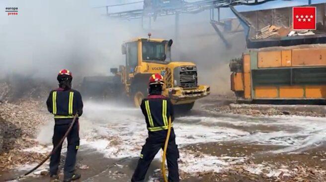 Bomberos trabajan en la extinción de un incendio de material para reciclaje almacenado en Alcalá (Madrid)