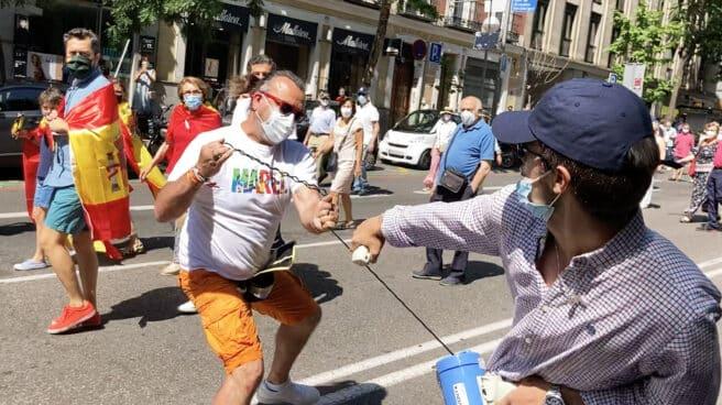 Momento en el que una persona le quita el megáfono al manifestante para estamparlo contra el suelo