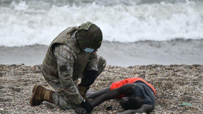 Un militar español atiende a un migrante en la costa de Ceuta
