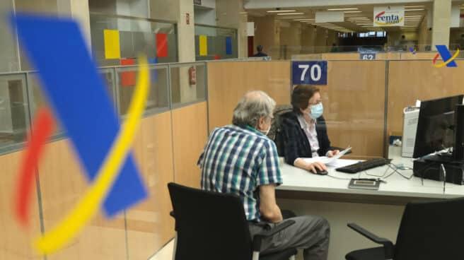 Un hombre haciendo la declaración de la renta con una empleada de la Agencia Tributaria