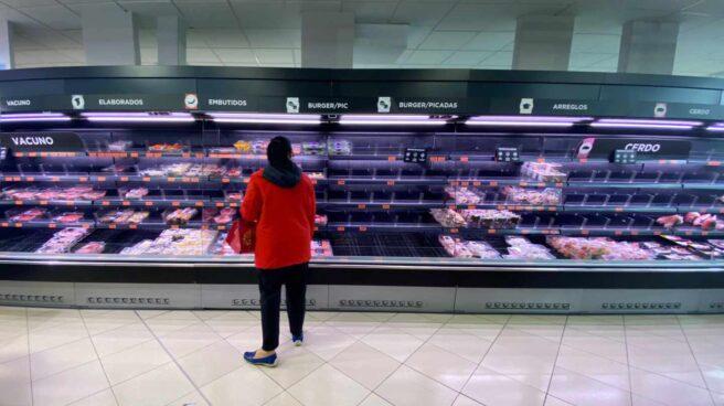 Una mujer observa los alimentos que quedan en los refrigeradores de carne de un supermercado un día marcado por colas de gente deseosas de hacer acopio de alimentos y otros productos debido al avance del coronavirus.