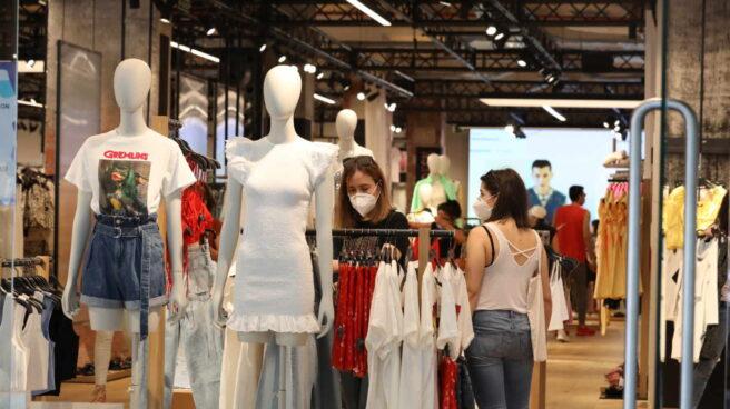 Personas con mascarilla en el interior de una tienda de ropa.