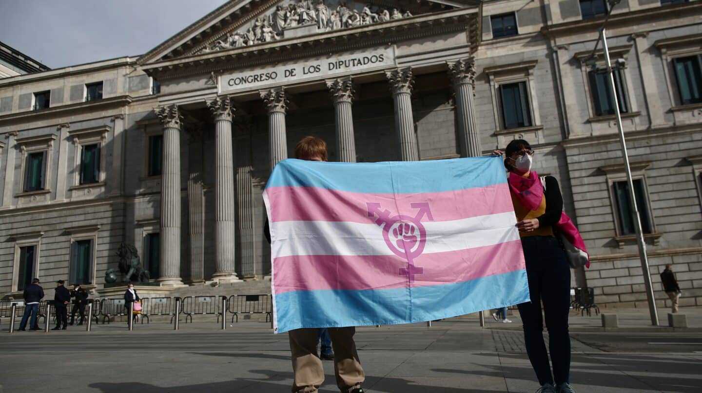 Dos personas sostienen una bandera trans durante una concentración convocada frente al Congreso.
