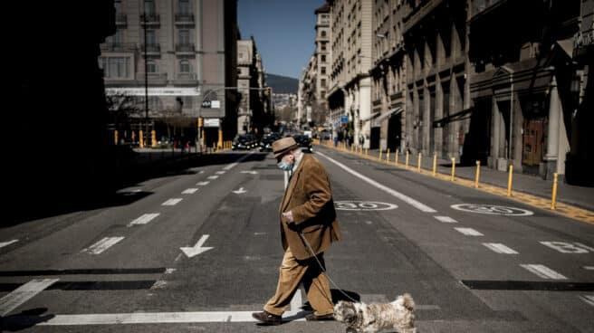 Un hombre con una mascarilla pasea a su perro cruzando una calle de Barcelona.