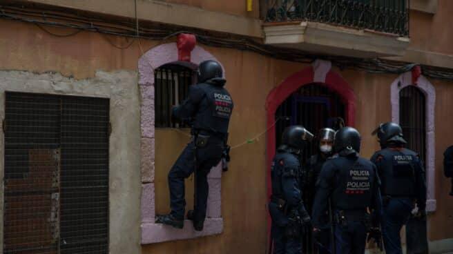 Agentes de Mossos d'Esquadra entran en casa de un vecino de Barcelona desahuciado.