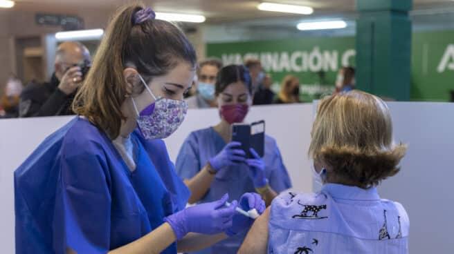 Una sanitaria vacuna a una mujer en el Estadio de La Cartuja de Sevilla.