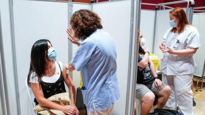 Dos personas reciben la primera dosis de la vacuna de Pfizer-BioNTech contra el Covid-19, en Leganés.