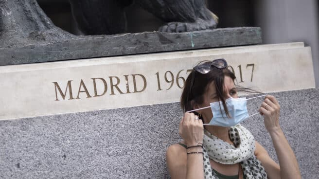 Una mujer se quita la mascarilla.