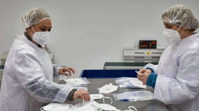 Dos operarias, en una planta de producción de mascarillas FFP2 en Madrid.